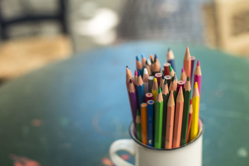 Close-Up Of Colorful Pencils In Container On Table