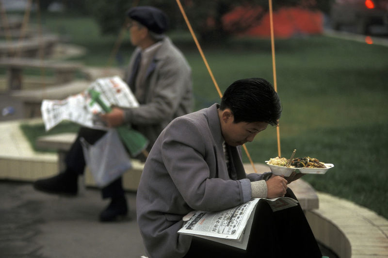 Businessman reading newspaper while holding food plate