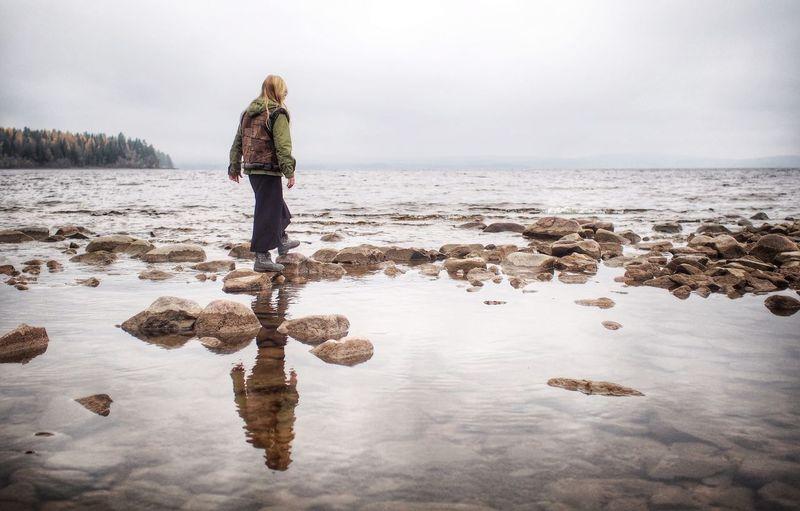 Woman walking on rocky beach against sky