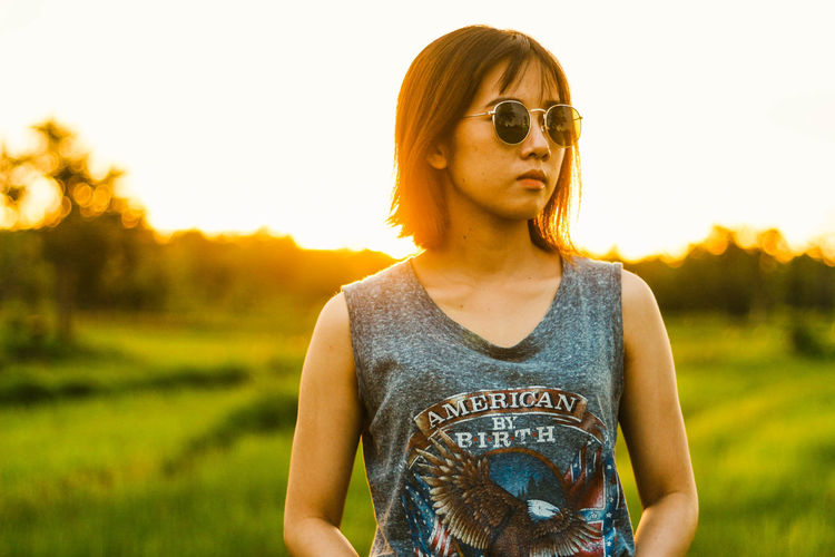 Young Woman Wearing Sunglasses While Standing On Field Against Sky During Sunset