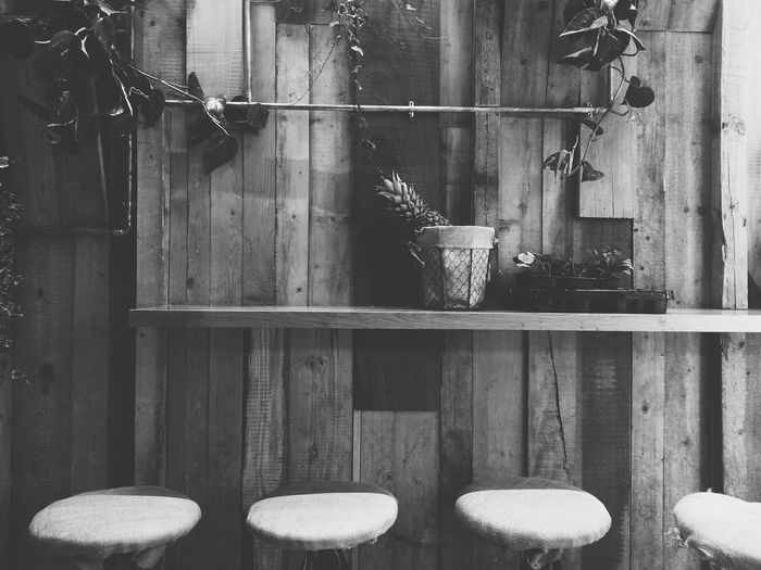 Empty stools by wooden wall at bar