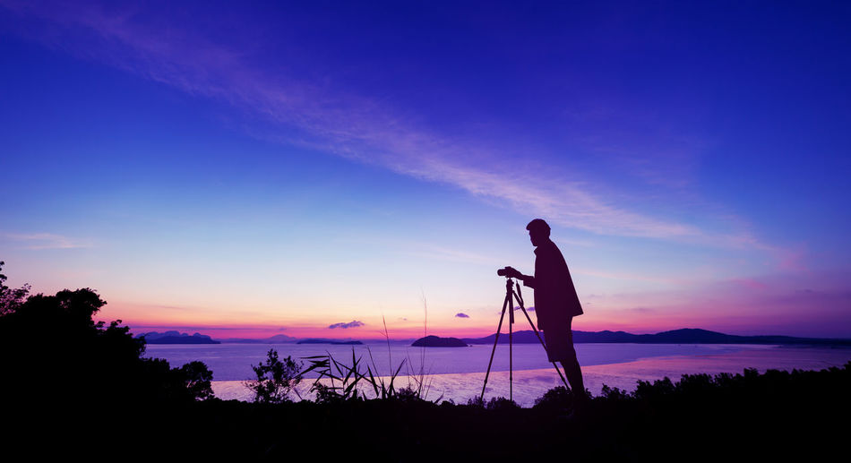 Beauty In Nature Camera - Photographic Equipment Cloud - Sky Digital Camera Full Length Land Men Nature Occupation One Person Photographer Photographing Photography Themes Real People Scenics - Nature Silhouette Sky Standing Sunset Technology Tripod