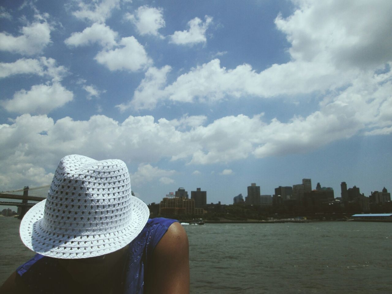 cloud - sky, hat, water, sky, leisure activity, architecture, real people, day, rear view, one person, lifestyles, sea, building exterior, headshot, women, built structure, outdoors, sun hat, nature, city, men, vacations, cityscape, people
