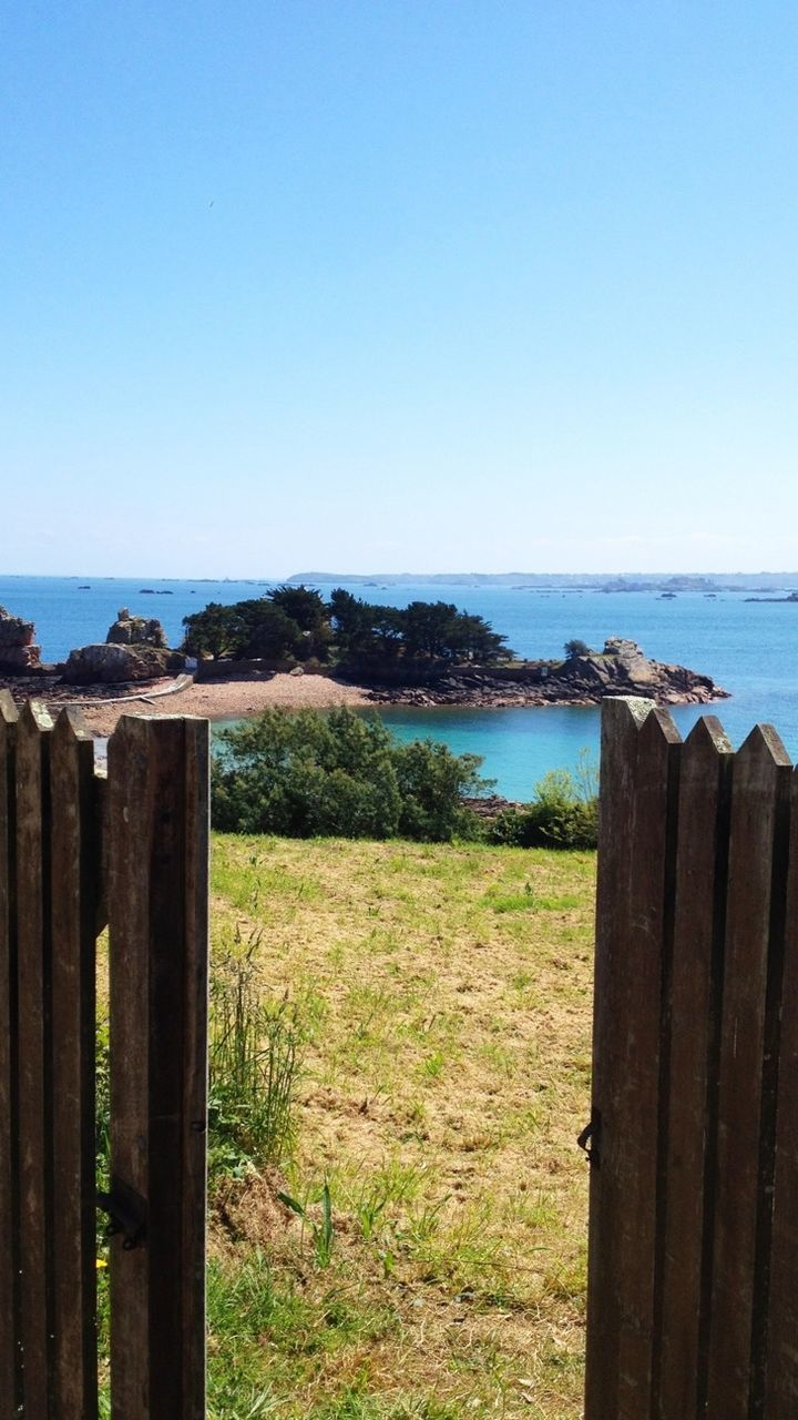 gate, wooden post, wood - material, no people, water, scenics, outdoors, day, nature, horizon over water, clear sky, tranquility, sea, beauty in nature, grass, sky