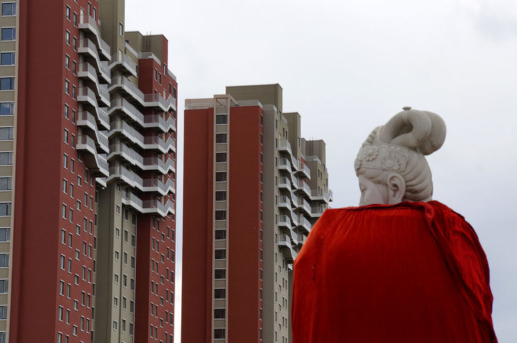Guanyin Statue Architecture Building Exterior Built Structure China City Day Housing Estate Low Angle View Modernism One Person Outdoors People Rear View Red Sculpture Sky Skyscraper Statue