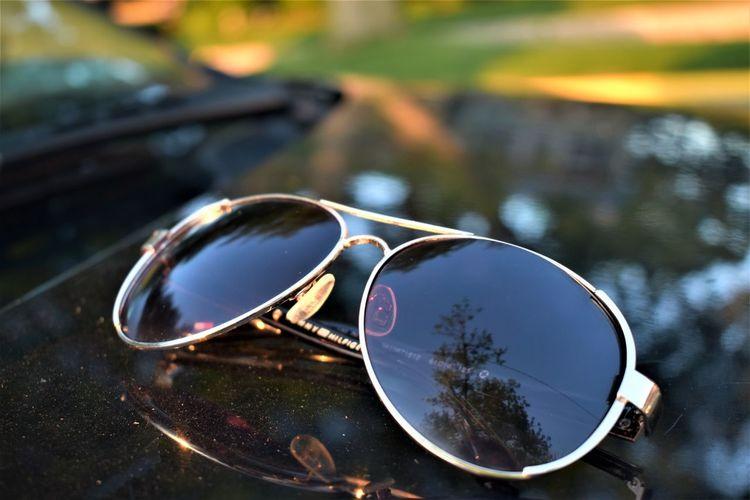 Close-up of sunglasses on vehicle bonnet