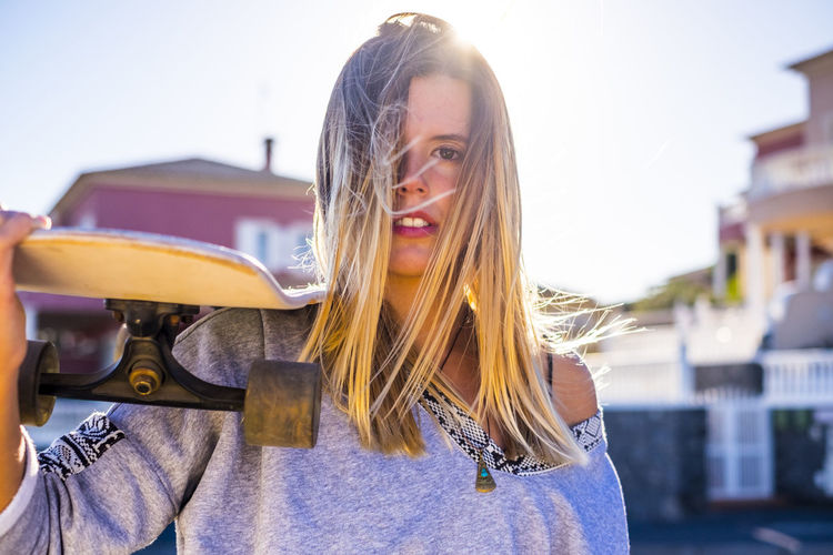 beautiful young caucasian woman looking at the camera with a skateboard on his shoulder. blonde hair and sun in backlight. houses defocused city location. alternative youth concept Hair One Person Young Adult Portrait Smiling Blond Hair Long Hair Sunlight Young Women Focus On Foreground Leisure Activity Happiness Hairstyle Day Lifestyles Beauty Women Real People Front View Beautiful Woman Outdoors Lens Flare Skateboarding Back Lit Caucasian