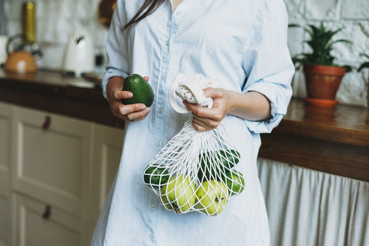 Midsection of woman holding fruits with mesh bag at home