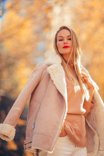 Portrait of beautiful woman standing in autumn