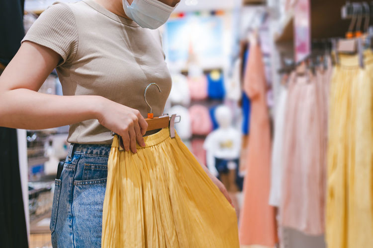 Midsection of woman standing at store