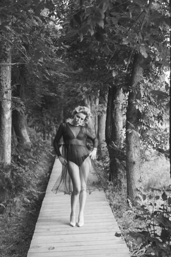 Portrait of woman with hands on hip standing on footpath at forest