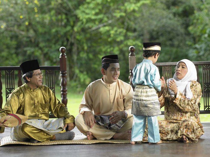 Family In Traditional Clothing Sitting On Mat