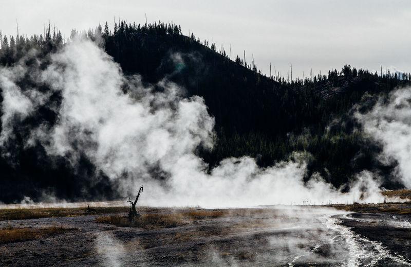 Steam On Landscape Against Silhouette Mountain Range