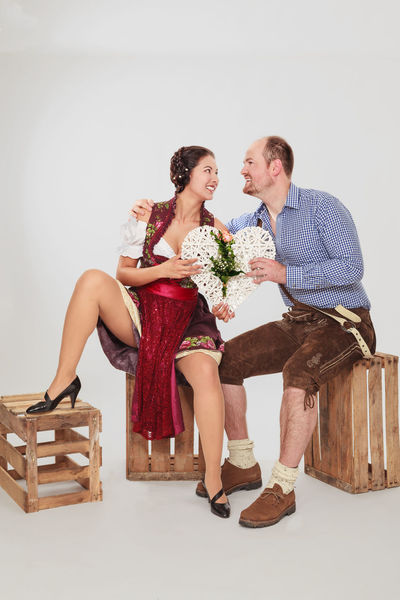Young loving couple sitting holding a white heart on old wine boxes in your midst. Adult Boxes Celebration Clothing Couple Dirndl Dress Fashion Fun Girl Glamour Happiness Love Loving Men Menfashion Midst Munich Old Portrait Stylish Traditional Two White Young