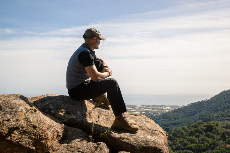 Side view of man looking at landscape while sitting on mountain against sky