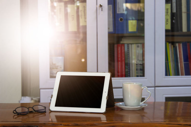 Mock up image of white tablet pc with black blank screen and coffee cup on wooden table in blur office or bookcase to work fast and modernize all types of teams in workspace. Business Communication Laptop Table Computer Connection Cup Wireless Technology Food And Drink Technology Window Office Desk Lens Flare Refreshment Sunlight Modern Workplace Culture Creative space Digital Composite Corporate Internet Education Mobile Love Student Workplace