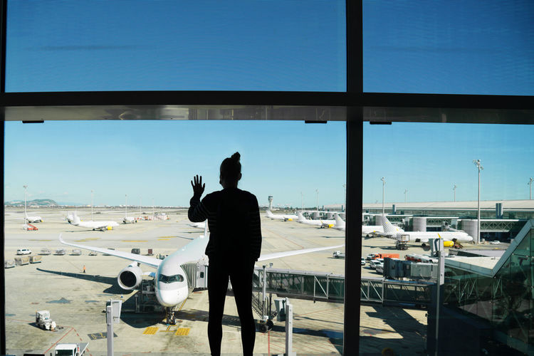 Woman standing by the window at the airport