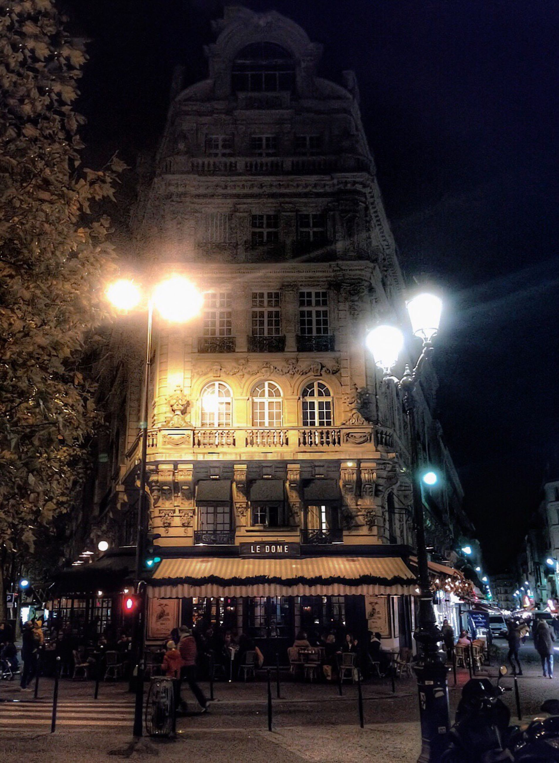 building exterior, illuminated, night, architecture, built structure, street light, street, city, lighting equipment, city life, incidental people, sky, building, city street, large group of people, low angle view, outdoors, car, road