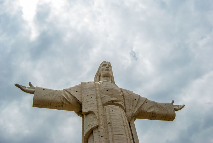 Low angle view of jesus statue against cloudy sky