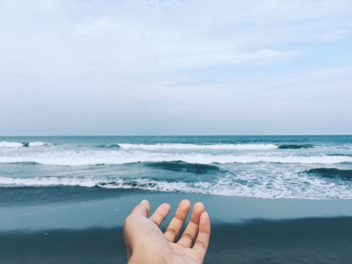 Midsection of hand by sea against sky
