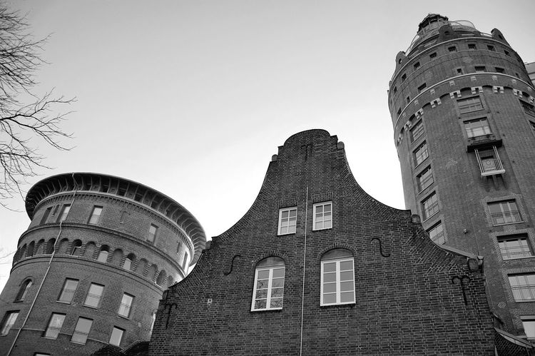 City Low Angle View Sky No People Outdoors Day MonochromePhotography Black & White Blackandwhite Monochrome Outdoor Photography Black And White Light And Shadow Architecture Built Structure Streetphotography Low Angle View Watertower Brick Brick Building Historical Historical Building Railing Ensemble