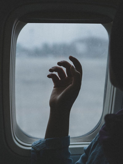 Low angle view of man sitting in airplane window