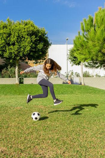 Full length of girl playing soccer ball on grass