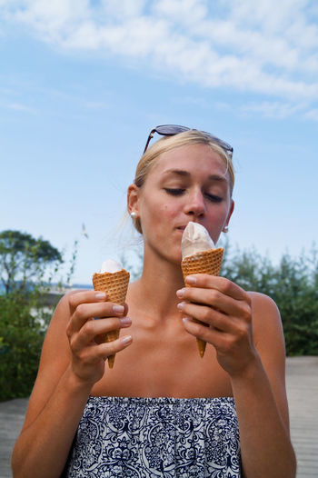 Young woman holding ice cream against sky