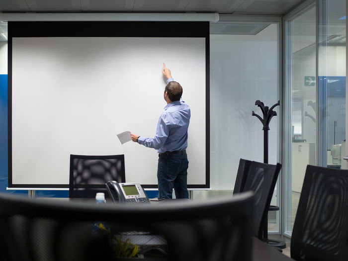 Rear view of businessman standing by projection screen in board room at office