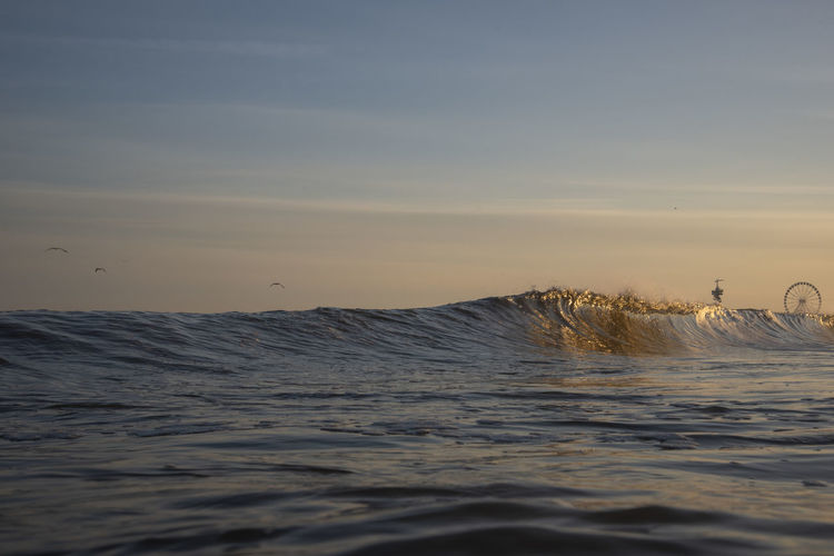 Close-up of waves rushing towards shore during sunset