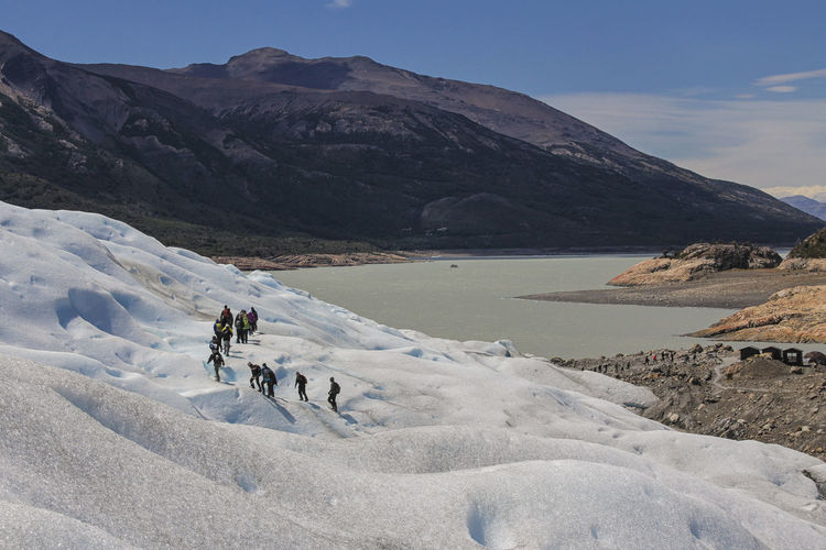 Mountain Beauty In Nature Real People Scenics - Nature Mountain Range Sky Nature Non-urban Scene Adventure Leisure Activity Sport Day Water Cold Temperature People Winter Travel Group Of People Men Riding Outdoors Glacier Trekking