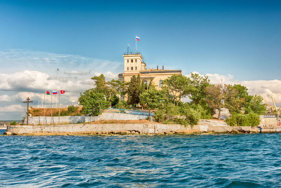 View of Pavlovsky Cape, iconic landmark in Sevastopol Bay, Crimea Architecture Building Building Exterior Built Structure Day Flag History Nature No People Outdoors Patriotism Sky The Past Tourism Tower Travel Travel Destinations Tree Water Waterfront