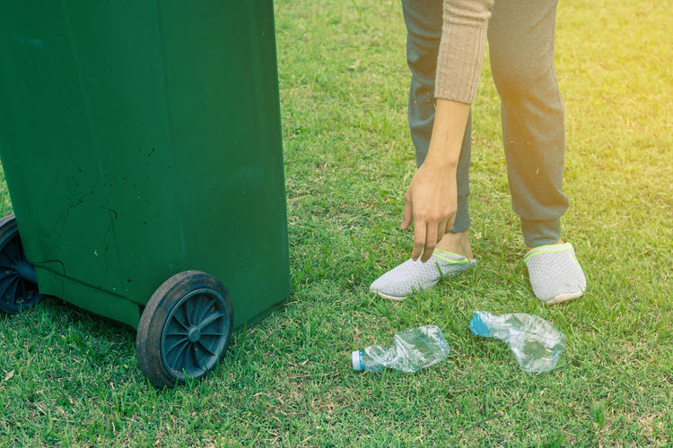 Low section of woman by garbage can picking up crushed plastic bottles on ground