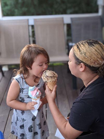 Girl feeding ice cream to sister
