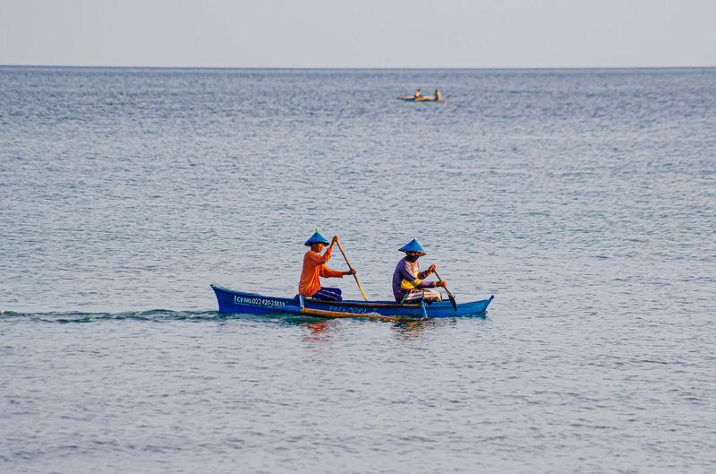 Men in boat on sea against sky