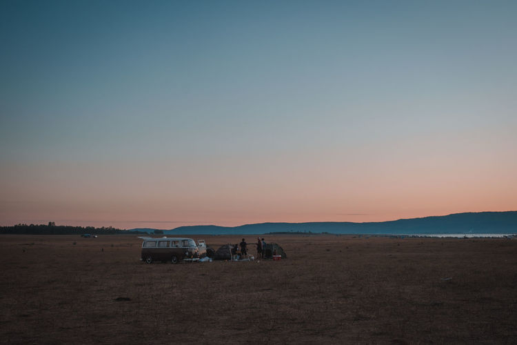 People and van by tents at campsite against sky during sunset