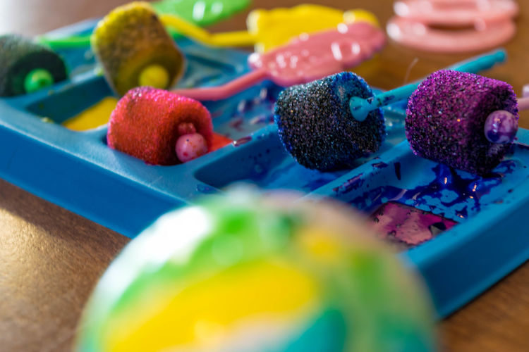 Colorful paint rollers in tray on table