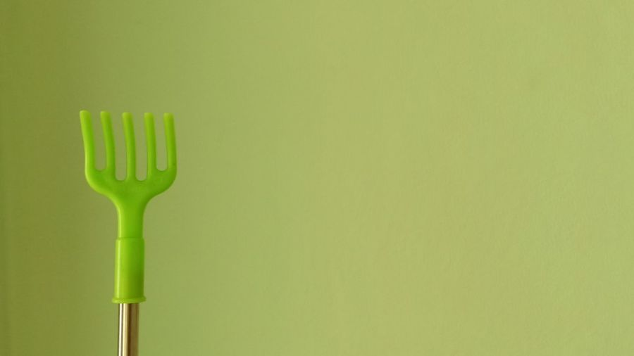 Close-up of green fork over white background