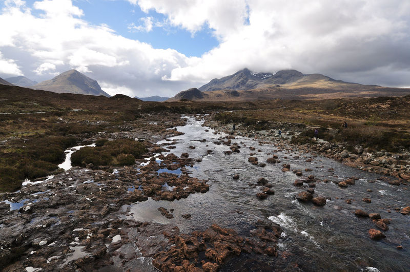 Scenic view of river stream and mountains at skye against sky