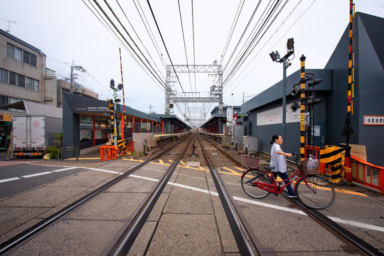 Man riding motorcycle on railroad tracks in city against sky