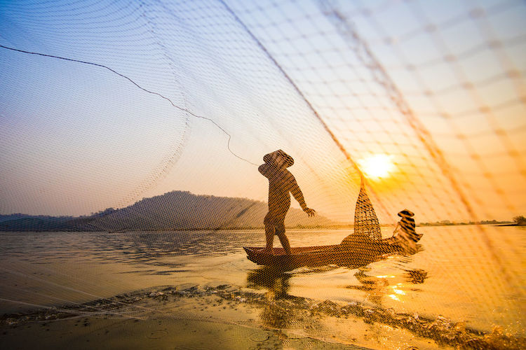 Man throwing fishing net in sea