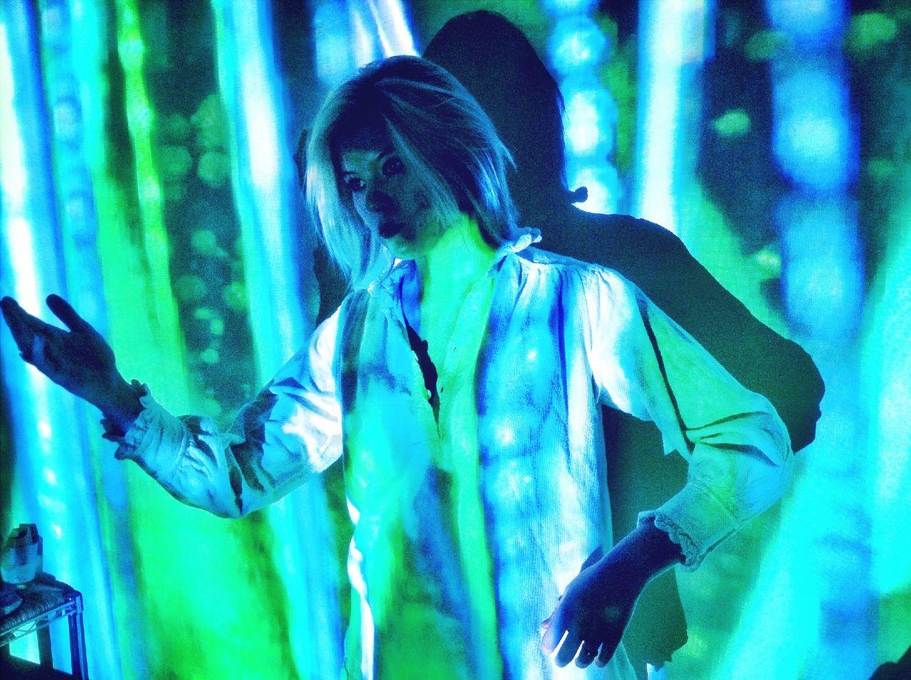 Woman Gesturing In Illuminated Room