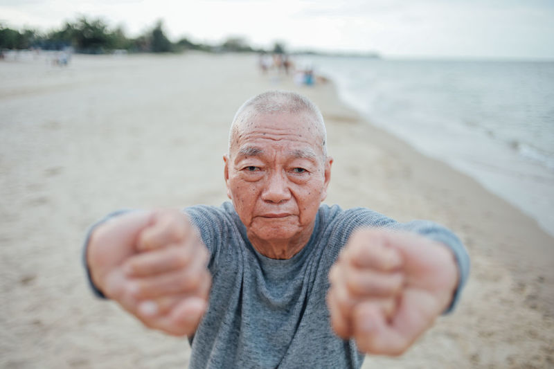 Portrait of senior man exercising while standing at beach against sky during sunset