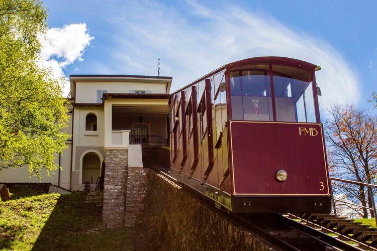 Train amidst buildings against sky