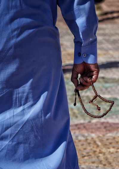 Midsection of man holding prayer beads in hands standing outdoors