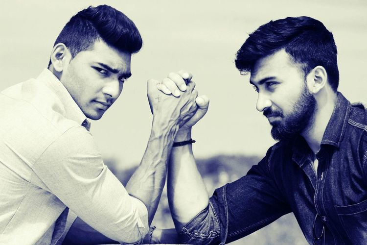 Portrait Of Man With Friend Arm Wrestling