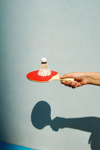 Close-up of hand holding umbrella on table against wall
