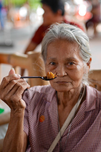 Portrait of senior woman eating food