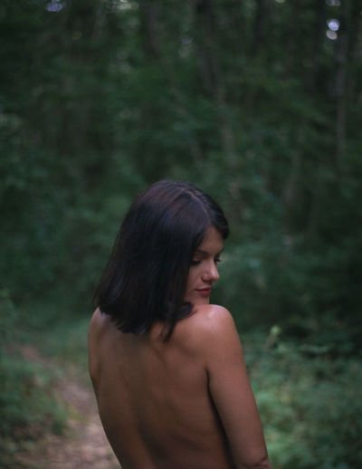 Rear view of shirtless woman standing in forest