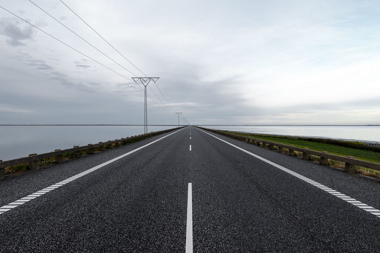 Cable Cloud - Sky Connection Day Diminishing Perspective Direction Dividing Line Electricity  Electricity Pylon Marking No People Outdoors Power Line  Power Supply Road Road Marking Sign Sky Symbol Technology Telephone Line The Way Forward Transportation vanishing point